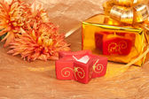 Chrysanthemum, gift and red candle on gold background — Stock Photo