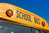 Front of yellow school bus against blue sky — Stock Photo