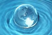 Glass globe in water — Stock Photo