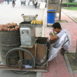 Chinese man selling veg anf having lunch along the road - ストック写真