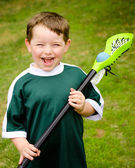 Happy young child lacrosse player with his stick — Stock Photo