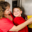 Mother and child putting up boy's art on family refrigerator at home — Stock Photo