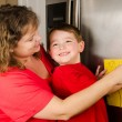 Mother and child putting up boy's art on family refrigerator at home — Stock Photo #10163619