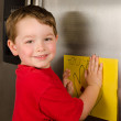 Child putting his art up on family refrigerator at home — Stock Photo