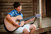 Dospívající chlapec hraje na kytaru na verandě historické kabiny — Stock fotografie