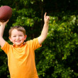 Child with football celebrating by showing that he's Number 1 — Stock Photo