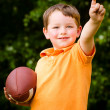 Child with football celebrating by showing that he's Number 1 — Zdjęcie stockowe