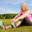 Middle-aged woman in her 40s stretching for exercise outdoors — Stock Photo