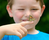 Spring concept with close up of a painted lady butterfly, Vanessa cardui, being held by child playing outdoors in nature — Stock Photo