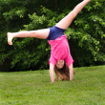 Young girl doing a cartwheel outdoors at park — Stock Photo #10342548