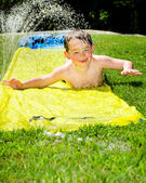 Happy child on water slide to cool off on hot day during spring or summer — Stock Photo