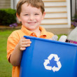 Recycling concept with young child carrying recycling bin to the curb at his house — Stock Photo #10422506