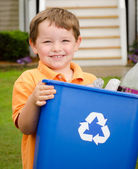 Recycling concept with young child carrying recycling bin to the curb at his house — Stock Photo