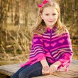 Winter or early spring portrait of pretty young girl child wearing knit poncho at park — Stock Photo #10460203
