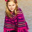 Winter or early spring portrait of pretty young girl child wearing knit poncho at park — Stock Photo #10460211