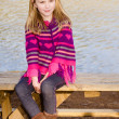 Winter or early spring portrait of pretty young girl child wearing knit poncho at park — Stock Photo
