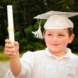 Young boy with cap and gown and certificate for preschool graduation — Stock Photo #10478170