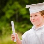 giovane ragazzo con cappuccio e abito e certificato per la laurea prescolare — Foto Stock