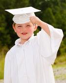 Muchacho joven con toga y birrete de graduación preescolar — Foto de Stock