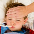 Sick child boy being checked for fever and illness while resting in bed — Stock Photo #10504513