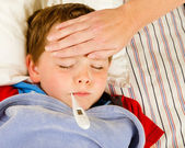 Sick child boy being checked for fever and illness while resting in bed — Stock Photo