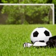 Stock Photo: Child sports concept with soccer ball, cleats, shin guards on field with copy space