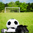 Child sports concept with soccer ball, cleats, shin guards on field with copy space — Stock Photo #10523742