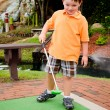 Stock Photo: Young boy plays mini golf on putt putt course