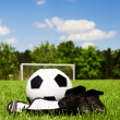 Child sports concept with soccer ball, cleats, shin guards on field with copy space — Stock Photo