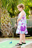 Young girl playing mini golf on putt putt course — Foto de Stock