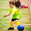 Young child boy playing soccer during organized league game — Stock Photo