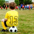 Young boy child in uniform watching organized youth soccer or football game from sidelines - Stock Photo