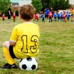 niño joven en uniforme viendo organizado fútbol juvenil o juego de fútbol de un lado — Foto de Stock