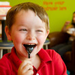 Young boy eating chocolate frozen yogurt at frozen yogurt or ice cream shop — Stock Photo