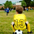 Young boy child in uniform watching organized youth soccer or football game from sidelines — Stock Photo