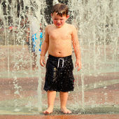 Unhappy child in water fountains at Centennial Olympic Park in Atlanta, Georgia, on hot day during summer. — Stock Photo