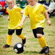 Children playing soccer in organized youth game - Stock Photo