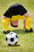Young child watches soccer ball go through his legs during organized youth game — Stock Photo