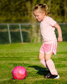 Cute young girl in pink playing soccer on field — Stock Photo
