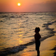 Child playing on beach at sunset — Stock Photo
