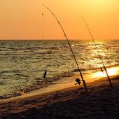 Rybářské pruty, které jsou nastaveny na pobřeží na pláži při západu slunce — Stock fotografie