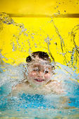 Young boy or kid has fun splashing into pool after going down water slide during summer with copy space — Stock Photo