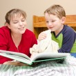 Mother reads bedtime story to young boy in his room at night — Stock Photo
