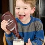 jonge jongen gieten gratis suikerstroop om chocolade melk aan diner tafel — Stockfoto #9677450