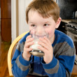 Young boy drinking milk at dinner table — Stock Photo