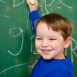 Stock Photo: Portrait of young boy after writing on chalkboard for school homework