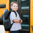 Happy young boy in front of school bus going back to school  — Стоковая фотография
