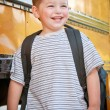 Foto de Stock  : Happy young boy in front of school bus going back to school