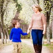 Mother and son at park during spring with flowering trees — Stock Photo