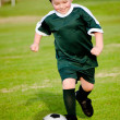 Young boy playing soccer in organized league game — Stockfoto
